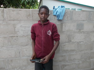 A sponsored child modelling uniform donated by Queen Eleanor Primary School.