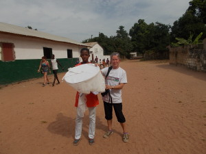 Anne presents a mosquito net to Awa - a Penyem resident. This is one of the many nets funded by Moulton Primary School.